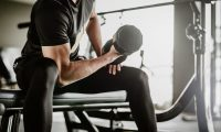 Man working out with a dumbbell in a gym